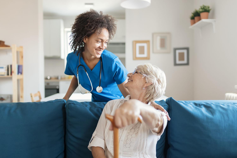 Healthcare worker assisting elderly woman